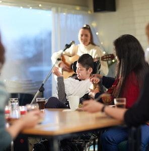 Cafegjester rundt et bord med en dame som spiller gitar og synger i bakgrunnen