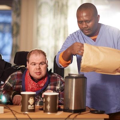 Mann bryterstyrer kaffekvern, mens en ansatt fyller oppi kaffebønner