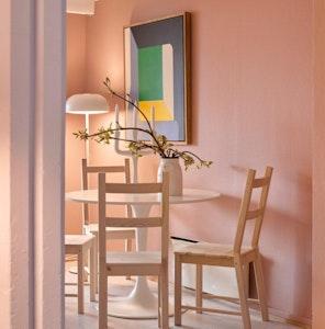 En stue med stoler, bord, blomst og et bilde